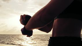 Closeup view of woman getting her fists ready for the boxing gloves by wrapping bandage around them standing against the stock footage