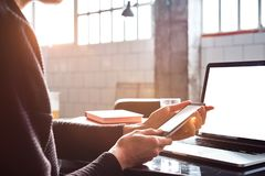 Closeup view woman hands using mobile smartphone and laptop. Space for design layout. Loft interior daylight. stock images