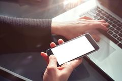 Closeup view woman hands using mobile smartphone and laptop. Space mockup for design layout. Loft interior sunlight. stock image