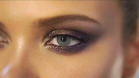 Closeup view of woman`s eyes with beautiful golden makeup opening in slowmotion.  stock video