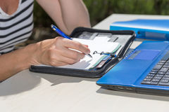 Closeup view of a woman's hand writing outdoors. Closeup view of a woman's hand writing by blue pen to the paper diary. Open notebook on the table. All is Royalty Free Stock Photo