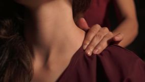 Closeup view of woman`s neck and shoulders having thai massage in spa by an unrecognizable female massagist. Healthcare