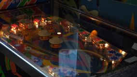Closeup view of working classic table pinball in museum of old slot-machines. Closeup view of working classic table pinball with colorful lighting in museum stock footage