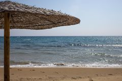 Closeup View of Woven Thatched Roof Umbrella Standing alone on the Beachfront. Footprints on Fine Sand and Wavy Crystal royalty free stock photos