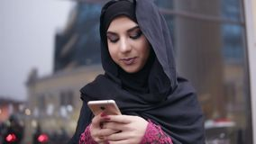 Closeup view of young attractive woman wearing hijab standing in the street, typing a message on her mobile phone