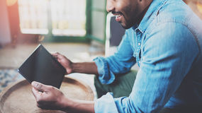 Closeup view of young bearded African man using tablet while sitting on sofa at home.Concept people working with mobile Royalty Free Stock Photography