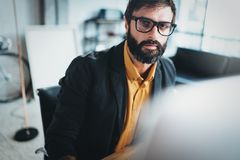 Closeup view of Young bearded designer using laptop computer at modern coworking studio.Panoramic windows on blurred. Background.Horizontal Royalty Free Stock Images