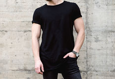 Closeup view of young bearded man wearing black tshirt and jeans posing in center of modern city. Empty concrete wall on Royalty Free Stock Photos