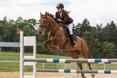 Closeup view of young blonde horsewoman jumping Royalty Free Stock Images