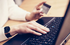 Closeup view of young businesswoman making online purchase via laptop, typing on keyboard and using her credit card. Horizontal,film effect, blurred background Stock Photography
