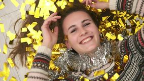 Closeup view of young happy smiling woman lying on the floor, the golden confetti falling on her. Slow motion shot.  stock footage