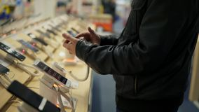 Closeup view of a young man`s hands choosing a new mobile phone in a shop. He is trying how it works