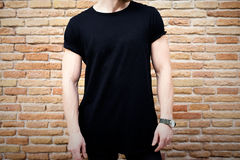 Closeup view of young muscular man wearing black tshirt and jeans posing outside. Empty brown grunge brick wall on the Stock Image