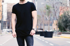 Closeup view of young muscular man wearing black tshirt and jeans posing on the street of the modern city. Blurred Royalty Free Stock Photos
