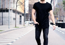 Closeup view of young muscular man wearing black tshirt and jeans walking on the streets of the modern city. Blurred. Background. Hotizontal mockup Royalty Free Stock Photography