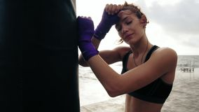 Closeup view of a young woman having a break after hard training by the boxing bag against the sun. Her hands are. Wrapped in purple boxing tapes. Training by stock footage