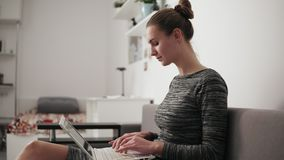 Closeup view of young woman at home sitting on the sofa, working with a laptop and typing text fast looking at the. Screen stock footage