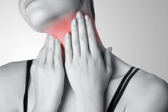 Closeup view of a young woman with pain on neck or thyroid gland. On gray background. Black and white photo with red dot Royalty Free Stock Images