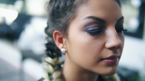 Closeup view of young woman sitting in the beauty studio while the makeup artist is correcting eyebrows using special. Brush. Slowmotion shot stock video footage