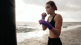 Closeup view of a young woman training with the boxing bag against the sun. Her hands are wrapped in purple boxing tapes. Training by the beach in summer stock video