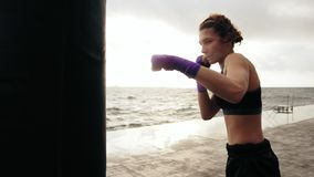 Closeup view of a young woman training with the boxing bag against the sun. Her hands are wrapped in purple boxing tapes. Training by the ocean in summer stock footage