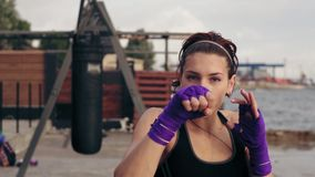 Closeup view of a young woman training with her hands wrapped in purple boxing tapes and looking in the camera. Training. By the beach in summer stock footage