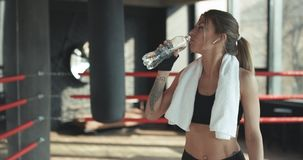 Closeup view of a young woman having a break after hard training by the boxing bag. Closeup view of a Young Woman In Wireless Earphones having a break after hard stock video footage