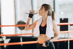 Closeup view of a young woman having a break after hard training by the boxing bag royalty free stock photography