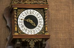 Vintage wall clock. Closeup of the vintage clock face hanging on brown wall Stock Image