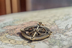 Closeup of vintage compass on old world map in front of heavy cu Stock Photos
