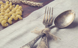 Closeup of vintage fork and spoon. Laying at the table with pasta and ears of wheat. Retro toned picture Royalty Free Stock Photography