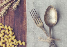 Closeup of vintage fork and spoon. Laying at the table with pasta and ears of wheat. Retro toned picture Royalty Free Stock Photo