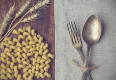 Closeup of vintage fork and spoon. Laying at the table with pasta and ears of wheat. Retro toned picture Stock Images