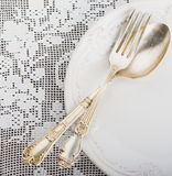 Closeup of vintage lacy white cloth handmade German silver fork and spoon Stock Photo