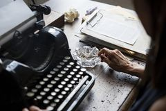 Closeup of vintage retro typewriting with hand and cigarette ashtray Royalty Free Stock Photo