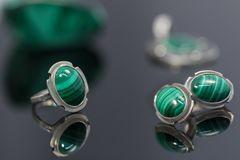 Closeup vintage silver earrings and ring with malachite on background of silver pendant and piece of malachite on black table. Closeup vintage silver earrings royalty free stock images