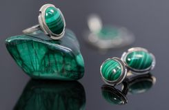 Closeup vintage silver earrings and ring with malachite on malachite stone piece on black acrylic desk. Royalty Free Stock Photography