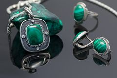 Closeup vintage silver pendant and earrings with malachite. On background of silver ring and piece of malachite on black acrylic board stock photo