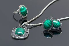 Closeup vintage silver pendant, earrings and ring with malachite. Closeup vintage silver pendant, earrings and ring with malachite on black acrylic plank stock photos