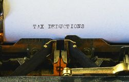 Closeup on vintage typewriter. Front focus on letters making TAX DEDUCTIONS text. Business concept image with retro office tool.  stock photography