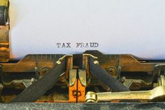Closeup on vintage typewriter. Front focus on letters making TAX FRAUD text. Business concept image with retro office tool.  royalty free stock images