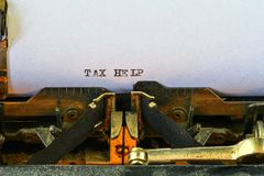 Closeup on vintage typewriter. Front focus on letters making TAX HELP text. Business concept image with retro office tool.  stock photos