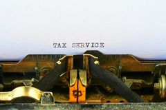 Closeup on vintage typewriter. Front focus on letters making TAX SERVICE text. Business concept image with retro office tool.  stock images