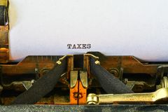 Closeup on vintage typewriter. Front focus on letters making TAXES text. Business concept image with retro office tool.  royalty free stock photos