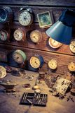 Vintage watchmakers workshop with clocks and tools. Closeup of vintage watchmakers workshop with clocks and tools royalty free stock image