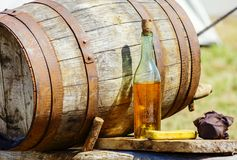 Vintage cider barrrel with bottle on table. Closeup of vintage wooden barrrel and cider bottle on table at outdoor stock photography