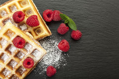 Closeup of waffles with raspberries on black slate Royalty Free Stock Photos