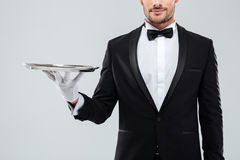 Closeup of waiter in tuxedo and gloves holding silver tray. Closeup of young waiter in tuxedo and gloves holding silver tray royalty free stock photos