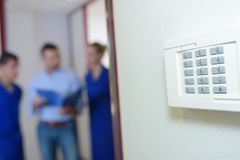 Closeup wall mounted keypad people in background. Closeup of wall mounted keypad, people in background Royalty Free Stock Image