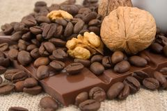 Closeup of walnuts, coffee beans and chocolate. Closeup of cup of coffee, walnuts, coffee beans and bar of chocolate over linen canvas Stock Photos